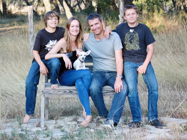 Die Johnson-Familie sitzt auf einer Holzbank im Freien.