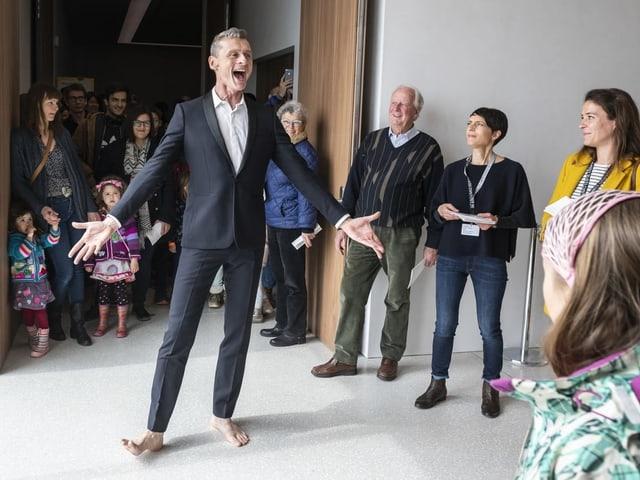 Ein Mann im Anzug und ohne Schuhe singt umringt von Zuschauern.