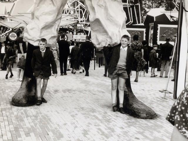 Schwarz-Weiss Fotografie mit zwei Buben, die neben den Füssen des Riesen Gulliver stehen.