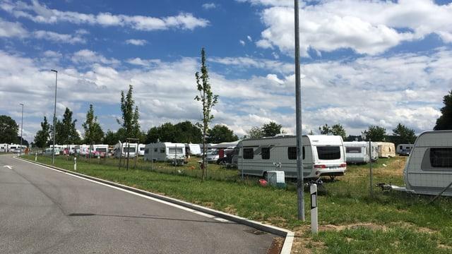 Viele Wohnwagen neben einem Parkplatz.