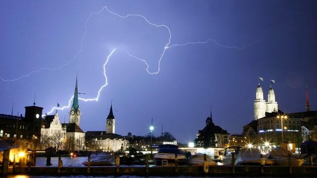 Ein Blitz über den Zürcher Kirchen Fraumünster und Sankt Peter.