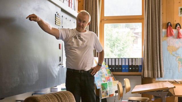 Ein Lehrer steht vor einer Wandtafel und erklärt etwas.