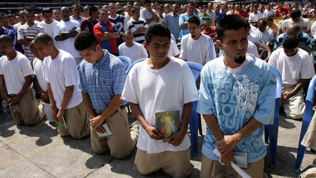 Hunderte Junge Männer sind versammelt, die vorderen Reihen knien auf dem Boden.