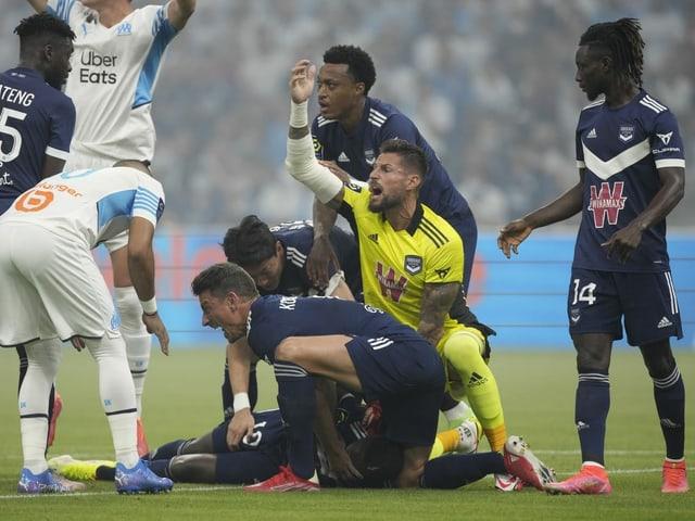 Samuel Kalu nach seinem Zusammenbruch umringt von Mit- und Gegenspielern.