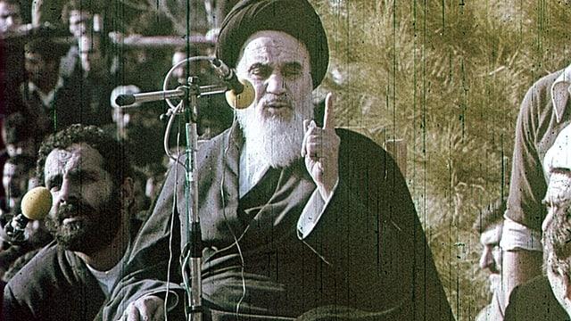 Ajatollah Chomeini steht am Mikrofon und hält eine Rede.
