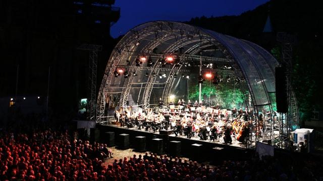 Orchester spielt bei Nacht auf einer Openair-Bühne
