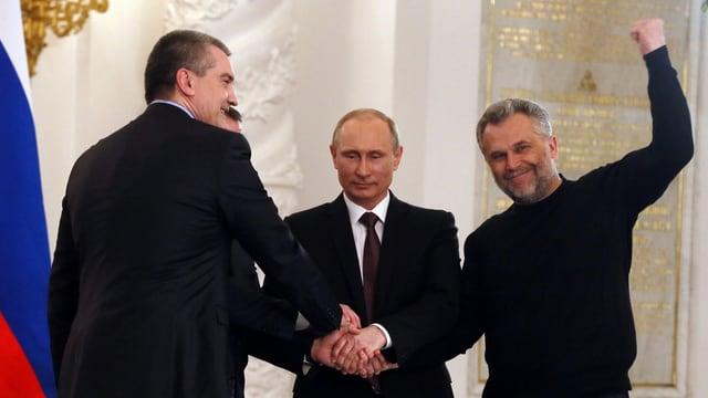 Präsident Putin (mitte), und die Krim-Führung Wladimir Konstantinow und Sergei Aksyonow sowie der Bürgermeister der Hafenstadt Sewastopol schütteln sich die Hände nach der Unterschrift. (keystone)