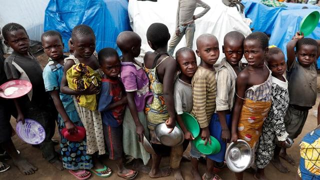 Kinder stehen in einem Flüchtlingslager mit Schüsseln Schlange.