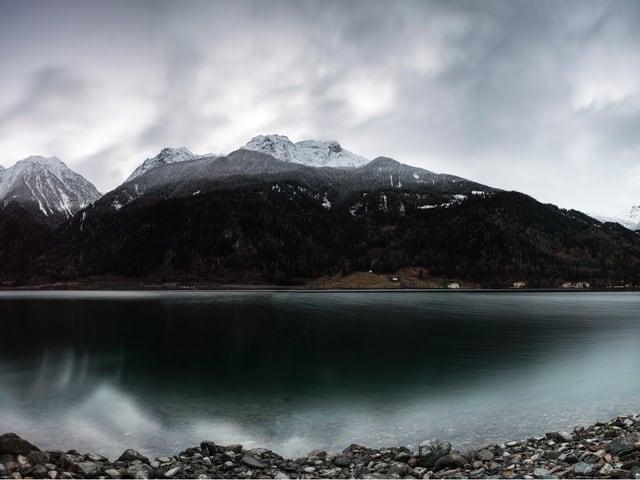 Ein See und ein Berg dahinter, dessen Spitze eingeschneit ist.