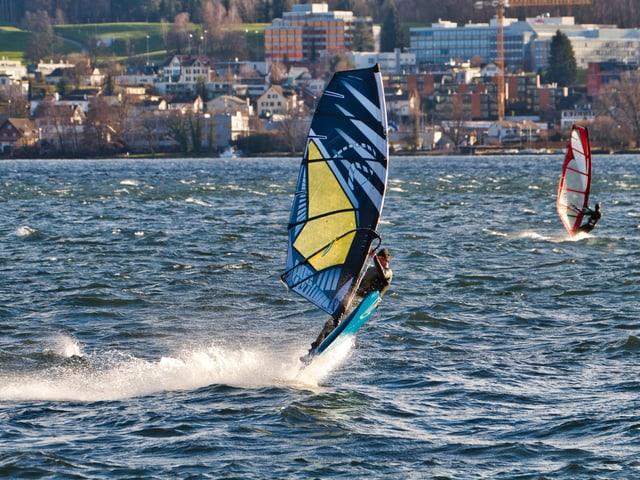 Windsurfer auf einem See mit viel Wind.