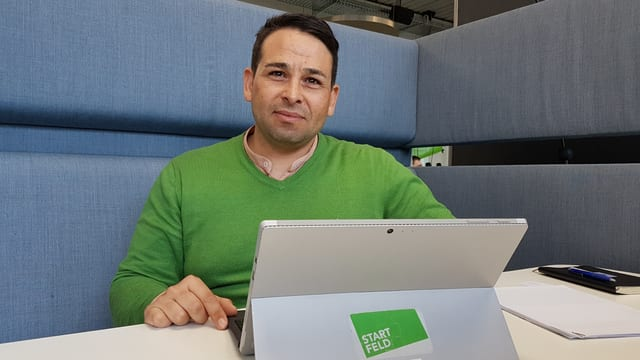Mann in grünem Pulli vor Tablet