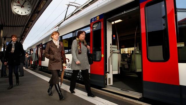 Zwei Frauen gehen neben eine Zug.