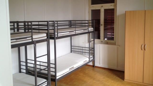 Ein Zimmer mit zwei Doppelbetten und einem Schrank.
