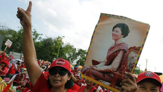 Thailänder – rot gekleidet – tragen Bilder in den Händen und schreien Parolen.