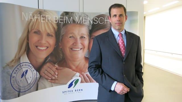Philip Steiner vor einem Plakat der Spitex Bern.