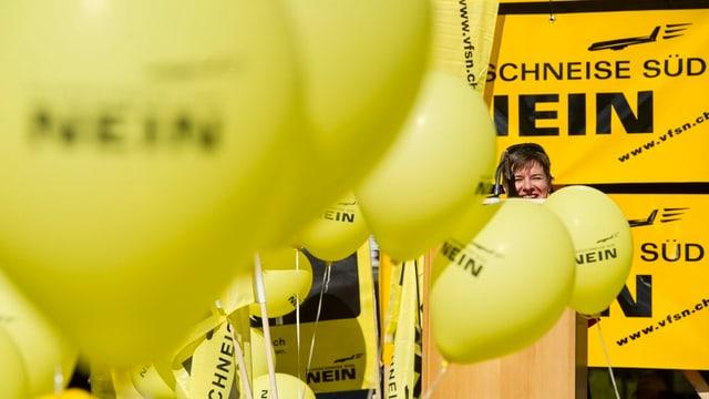 Claudia Nielsen am Rednerpult, inmitten von gelben Ballonen.