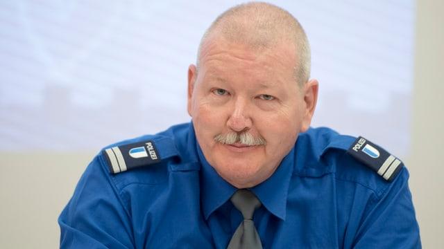 Brustbild eines älteren Mannes in blauem Hemd mit Polizeiabzeichen.