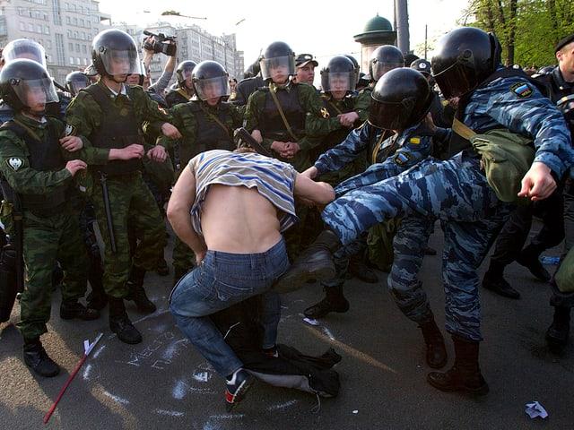 Polizisten, die mit Fusstritten einen Demonstranten malträtieren.