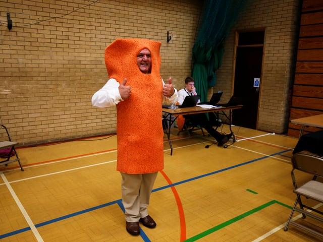Mann in orangem Fischstäbchen-Kostüm in Turnhalle mit Wahl-Urne.