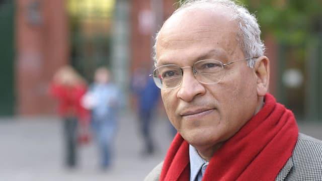 Gamal al-Ghitani trägt einen roten Schal und eine randlose Brille.