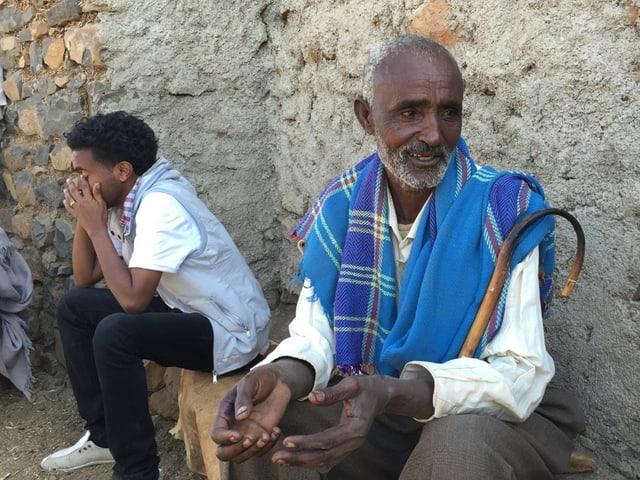 Ein alter Mann in weissem Hemd und Gehstock sitzt an einer Hauswand, neben ihm ein Junge in westlicher Kleidung.
