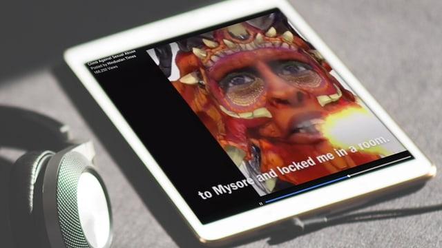Tablet, daneben Kopfhörer: Auf dem Bildschirm eine Frau mit drachenartiger Maske im Gesicht.