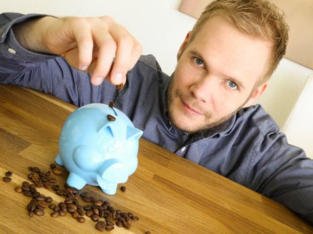 Stefan Siegenthaler lässt Kaffeebohnen aufs Sparschwein fallen.