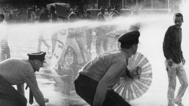 Zwei Polizisten ducken sich vor dem Wasserstrahl eines Wasserwerfers.