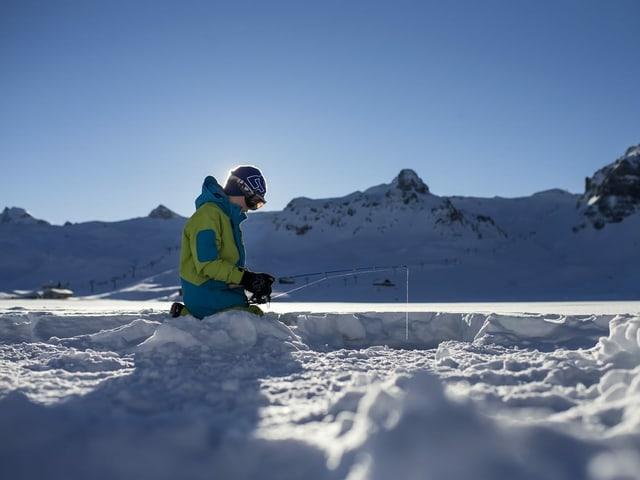 Ein Junge kniet auf einem gefrorenen See und hält eine Angel in ein Eisloch.