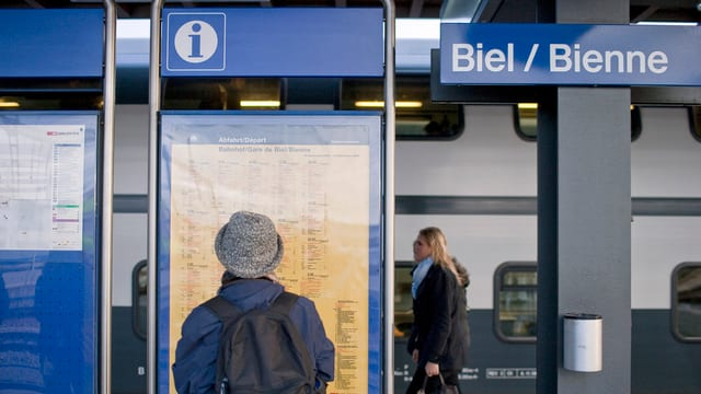 Person vor einem Fahrplan im Bahnhof Biel.