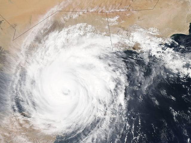 Ein Satellitenbild des Wirbelsturms mit einer sichtbaren Vertiefung im Zentrum des rotierenden Systems. Während der Himmel über dem Golf von Aden stark bewölkt ist, sieht man die Wüste der Arabischen Halbinsel.