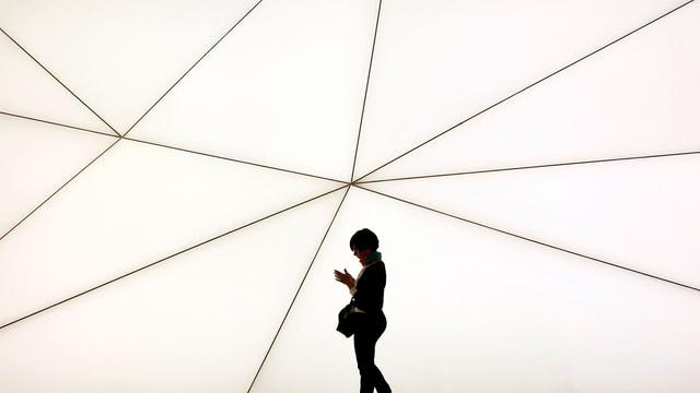 Eine Frau schaut auf ihr Mobiltelefon während sie am Samsung-Stand am Mobile World Congress in Barcelona vorbeiläuft.