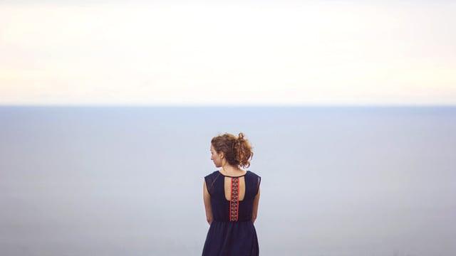 Eine Frau vor einem weiten Horizont mit Meer