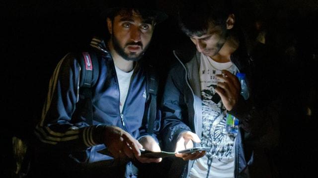 Zwei syrische Flüchtlinge im Dunkeln, ihre Handy-Displays leuchten, einer schaut hoch.