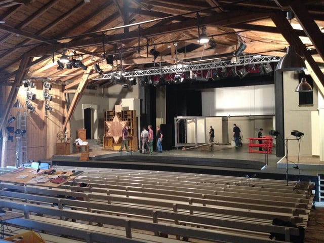 Bühne, darüber Holzbalken, davor Holzbänke