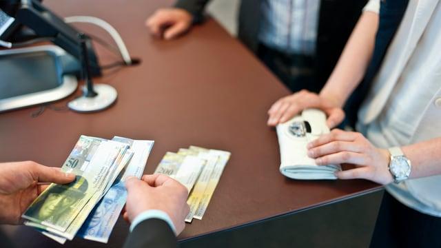 Ein Bankangestellter zahlt einer Kundin Bargeld in Form von Noten aus.