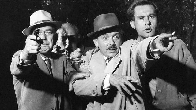 Vier Männer schauen ins Ungewisse: Einer zeigt aus dem Bild, ein anderer hält eine Pistole in der Hand.