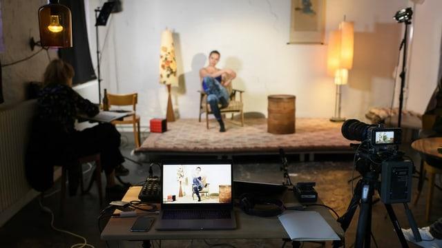 Eine Frau sitzt auf einer improvisierten Bühne und wird von einer Kamera gefilmt.