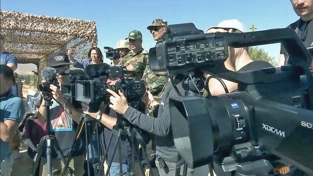 Eine Gruppe von Menschen mit Kamera, Mikrophon und Fotoapparat.