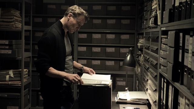 Ein Mann blättert in einem Archiv in einem Buch