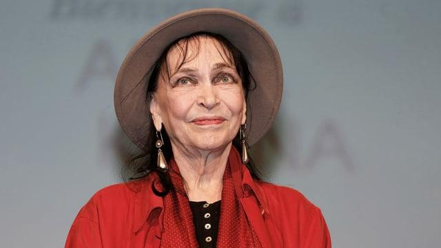Eine Frau mit Hut lächelt in die Kamera.