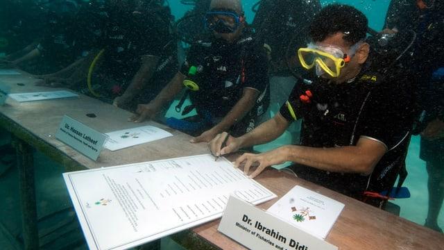 In einer Regierungssitzung unter Wasser unterzeichnete der Fischereiminister der Malediven in einem Taucheranzug einen Aufruf an die Welt, den CO2-Ausstoss zu senken.
