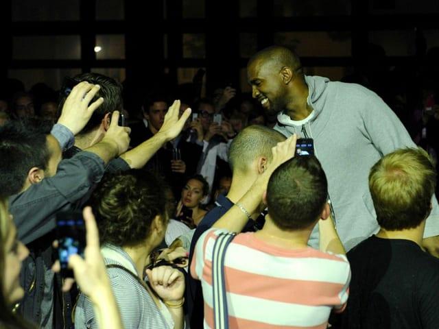 Fans des Rappers umringen Kanye West und fotografieren ihn mit ihren Smartphones.