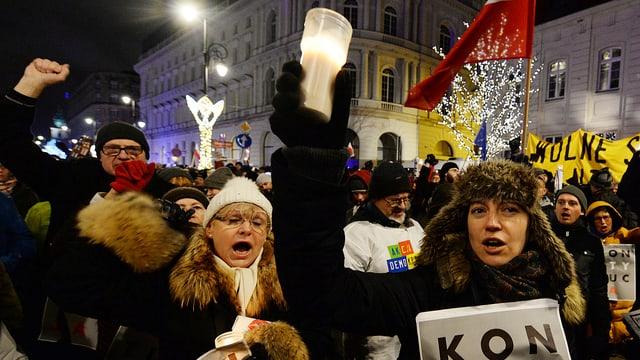 Demonstranten singen in der Nacht und halten Kerzen in die Luft.