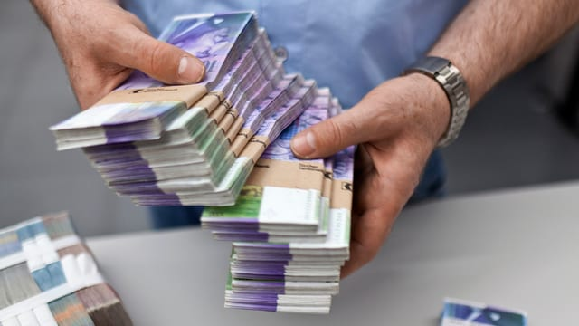 Mann mit Geldbündeln in den Händen.