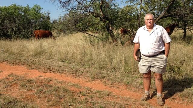 Weisser älterer Mann. Er steht auf seinem Land. Rote Erde. Im Hintergrund Kühe.