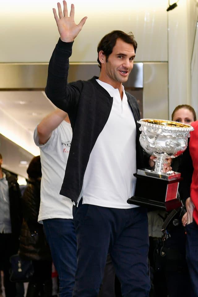 Roger Federer winkt mit dem Pokal.