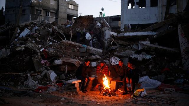 Obdachlose Palästenineser wärmen sich an einem Feuer