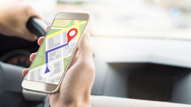 Mann im Auto schaut auf Smartphone mit geöffneter Navigations-App
