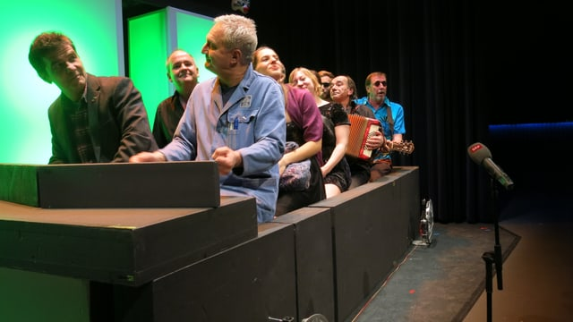Ein Auto Car aus Styroporelementen steht auf der Bühne. Darin sitzt die Crew de Rahmdäfeli und schaut gegen das Publikum.
